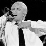 Anthony Kiedis black & white photo of him in shirt and tie singing on stage