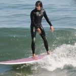 anthony kiedis standing on surfboard sea