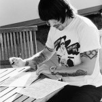 black and white photo of AK writing showing his arm tattoos