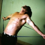Anthony Kiedis topless against green background