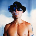 Anthony Kiedis topless wearing black hat and smoking
