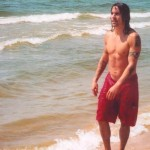 Anthony Kiedis topless on beach wearing red shorts