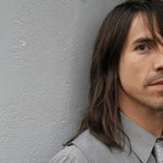Anthony Kiedis Red Hot Chili Peppers gray suit and tie against wall